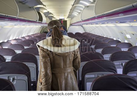 Young woman in airplane traveling to a tourist attraction