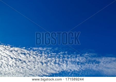 Texture of blue sky and happy clouds. Heavenly background in a highly patterned top. Free space atmospheric flight and freedom.