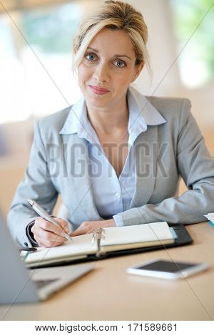 Businesswoman working in office on agenda