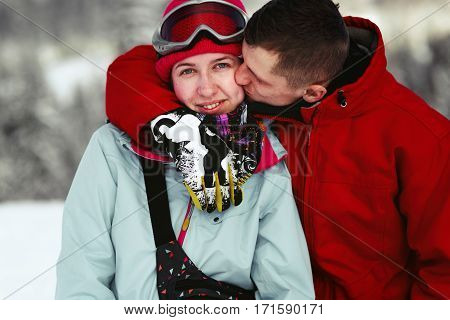 Man In Red Ski Jacket Kisses Woman's Pink Cheek And Hugs Her Neck Somewhere In Snowed Forest