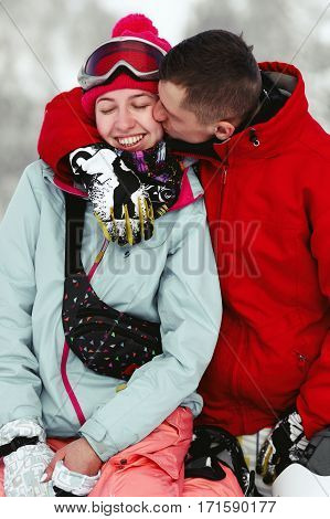 Man In Red Ski Jacket Kisses Woman's Cheek While They Sit On Snowed Hill