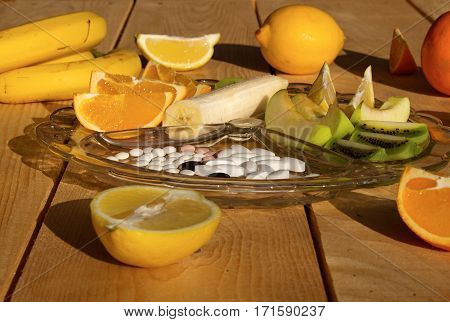 fresh sliced fruit on a glass plate on a wooden table and a lot of synthetic drugs bananas apples oranges lemons kiwi