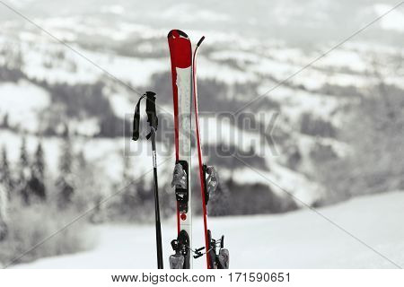 Red And White Skis Put In The Snow With Great Mountain View Behind Them