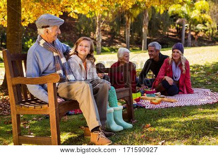 Family picnicking and the grandfather laughing with his grand daughter on a bench in a park
