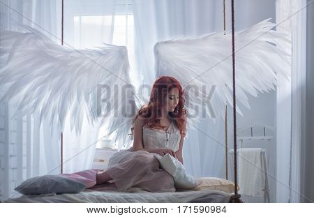 beautiful young model with open angel wings and pink dress sitting on hanging bed suspended from the ceiling . White loft interior.