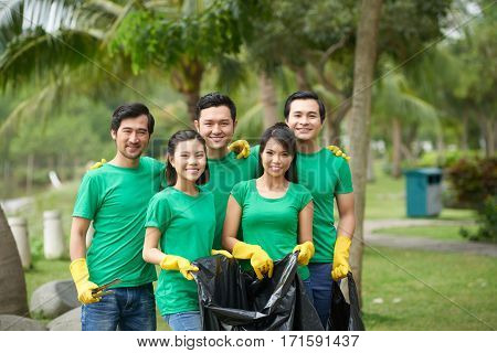 Cheerful group of friends looking at camera with wide smiles while collecting garbage in lovely green park