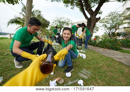 Joyful Asian woman sitting on haunches and picking up glass bottles in blooming park