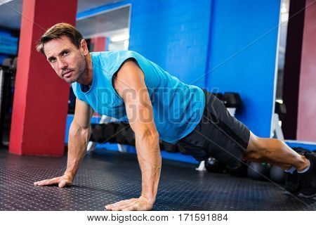 Portrait of serious athlete doing push-ups in gym