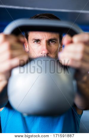 Portrait of serious man showing kettlebell in gym
