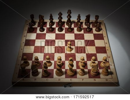 Classic Opening of Chess Game on Wooden Board. First Move, e2-e4.