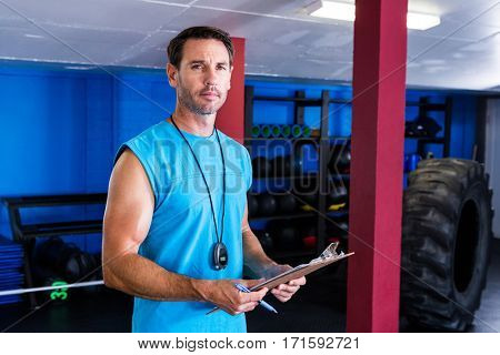 Portrait of serious fitness instructor holding clipboard in gym