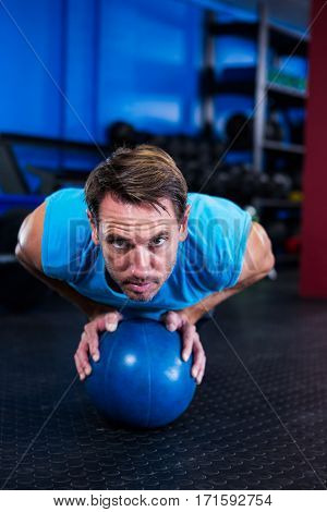 Portrait of serious athlete with ball while exercising in gym