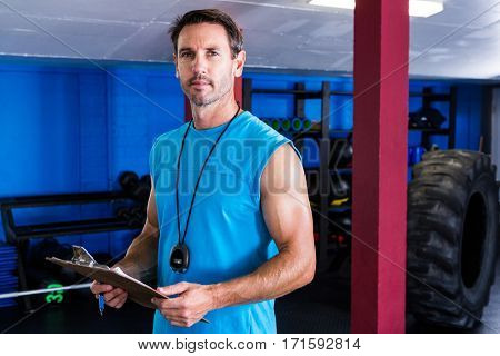 Portrait of serious instructor holding clipboard in gym