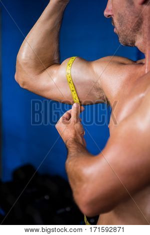 Close-up of shirtless athlete measuring biceps with tape measure in gym