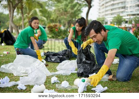 Portrait of middle-aged Asian man in casualwear crouching to plastic waste and picking it up in bin bag