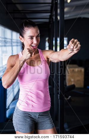 Smiling female athlete punching in gym