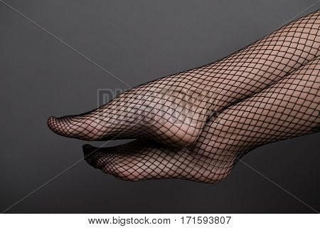 Woman feet with fishnet tights on a dark gray background