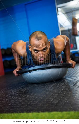 Portrait of serious athlete with BOSU ball while exercising in gym