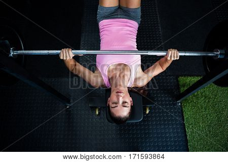 High angle view of athlete holding barbell while lying on bench press in gym