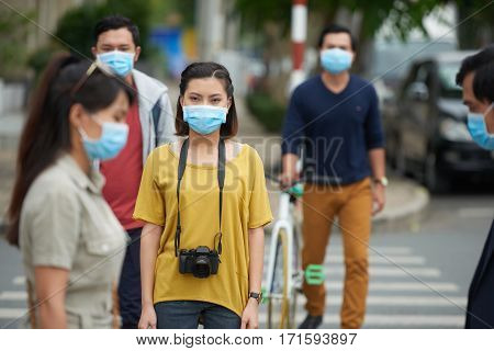 Danger of epidemic: Asian people wearing protective masks while crossing road in city center