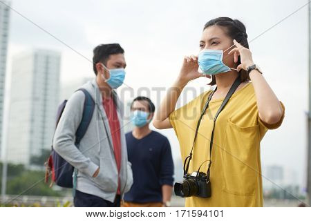 Waist-up portrait of Asian woman putting on protective mask while standing in city center and looking into distance