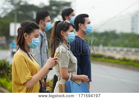 Profile view of two Asian women and three Asian men in protective masks standing on roadside of modern city