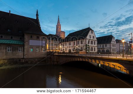 View of medieval bridge Ponts Couverts and Cathedral of Our Lady (Notre Dame) of Strasbourg at night in Strasbourg France
