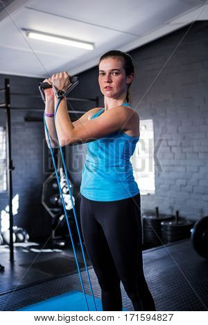Portrait of serious female athlete stretching resistance band while standing in gym