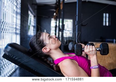 Female athlete holding dumbbell while lying on bench press in gym