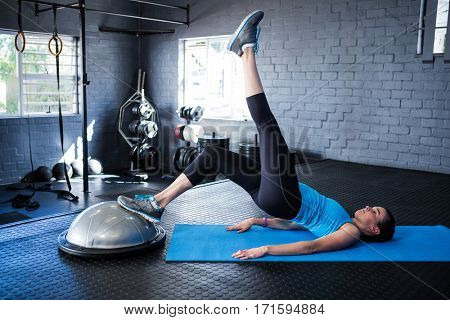 Full length of female athlete with BOSU ball while exercising in gym