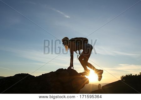 Woman Tourist With Backpack In Tourist Clothes Climbs Mountain. Silhouette Against Background Sunris