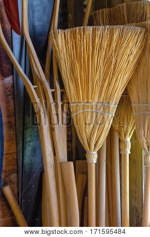 Handmade Straw Brooms Against Wall for Sale