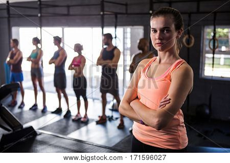 Portrait of female athlete with arms crossed while standing in gym