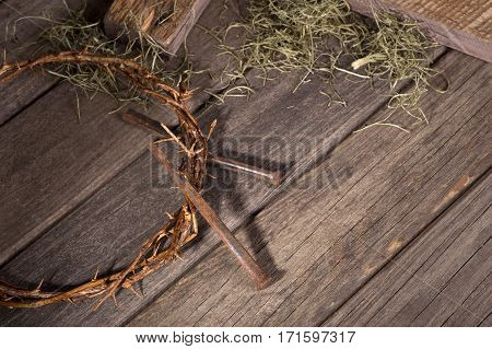 Crown of thorns and nails on a wood surface