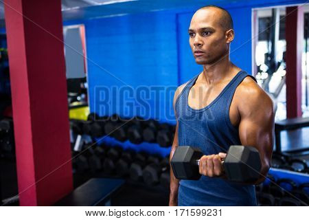 Determined man exercising with dumbbells in fitness studio