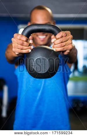 Happy man covering face with kettlebell while exercising in gym