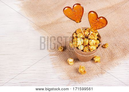 Paper bucket of caramel popcorn and two candies on a stick on a white wooden background. Lollipop in the shape of a heart. Copy space.