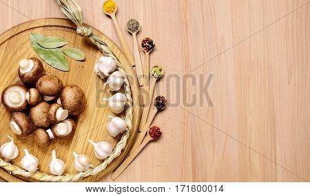 Braid of garlic mushrooms and bay leaves on a round cutting board light wooden table. Nearby are several small wooden spoons with different spices. Top view.