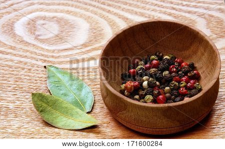 Fragrant colorful pepper in a wooden bowl and two dried bay leaves on a light wooden table.
