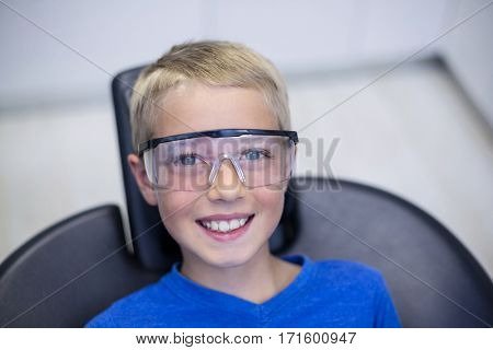 Smiling young patient sitting on dentist chair in dental clinic