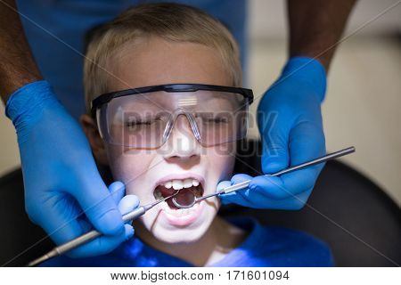 Dentist examining a young patient with tools in dental clinic