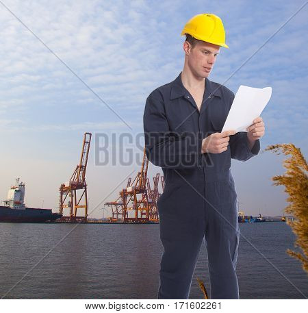 Young worker at harbor with cranes on background