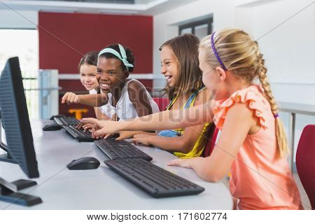 Schoolgirls having fun while using computer in classroom at school