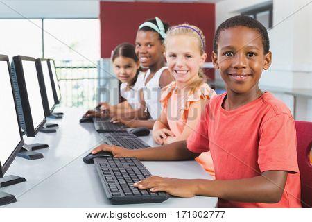 Portrait of happy school kids using computer in classroom at school
