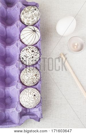 Decorating Easter eggs using a traditional wax-resist method and modern patterns. Eggs in a purple paper box with molten wax applied to the white shell. Stylus wax candle and one more egg not yet decorated lying aside on the table