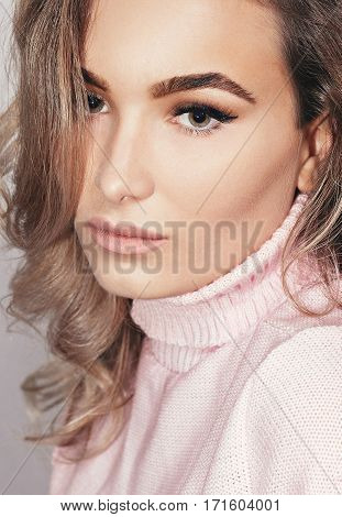 people beauty lifestyle fashion and sensitive concept - Closeup sensual portrait of beautiful girl in the studio. girl in a pink sweater hands near the face eyes closed