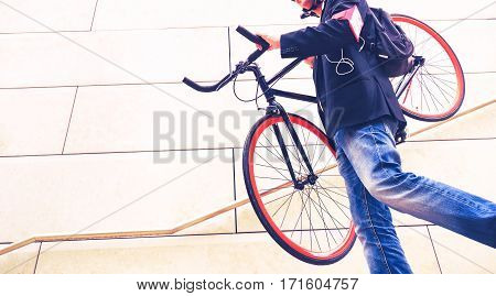Business man carrying sport bike on shoulders down steps - Worker commuter holding bicycle in city on modern urban wall background cropped image white copy space - Healthy concept of green transport