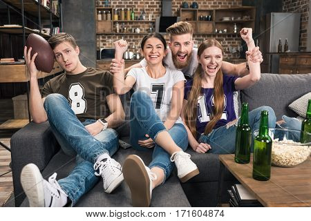 Excited young friends supporting favorite football team at home