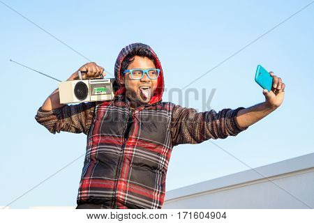 Funny selfie tongue sticking out of young indian man on blue sky background - Asian american street dancer guy having fun taking selfie listening at music out of vintage radio holding on shoulders