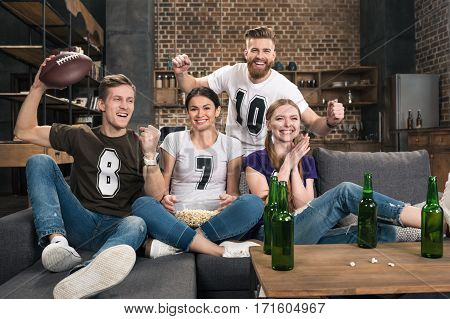 Excited young friends watching football match and supporting favorite team at home
